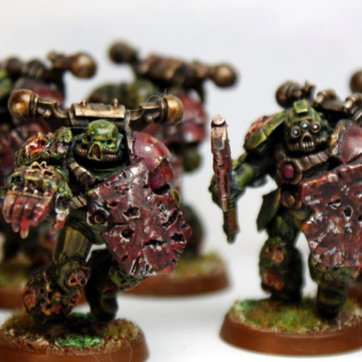 Blood and filth encrusted space marines with battered shields and melee weapons.